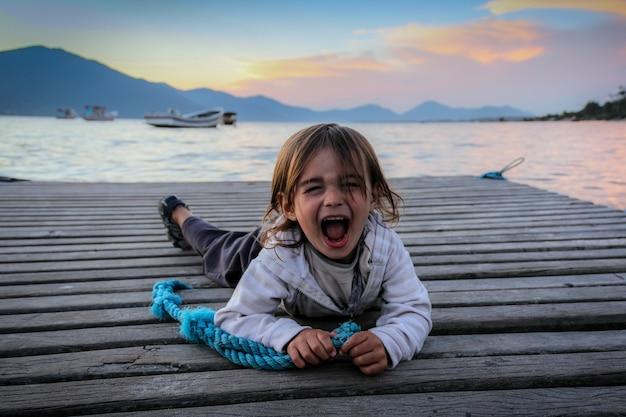 Portret van een kleine jongen die geamuseerd schreeuwt, liggend op een dok.