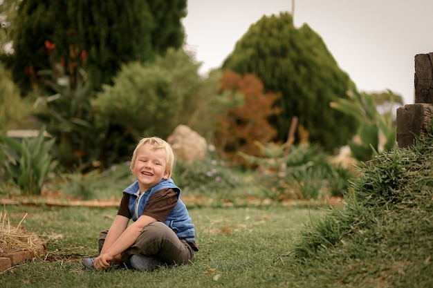 Portret van een kleine jongen die in een mooie tuin zit