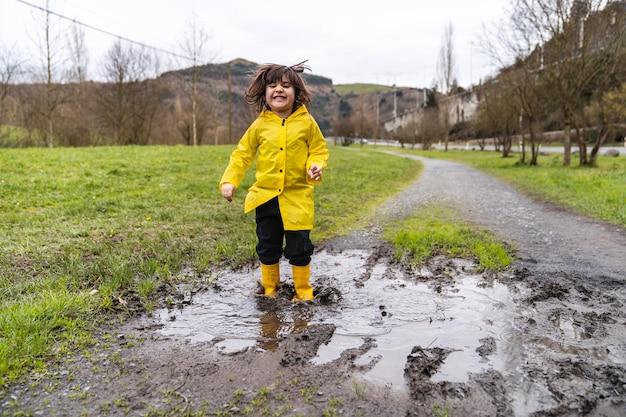 Portret van een kleine jongen die lacht en springt in een plas regenwater in een modderige plas op een weilandweg die een gele regenjas en gele regenlaarzen draagt