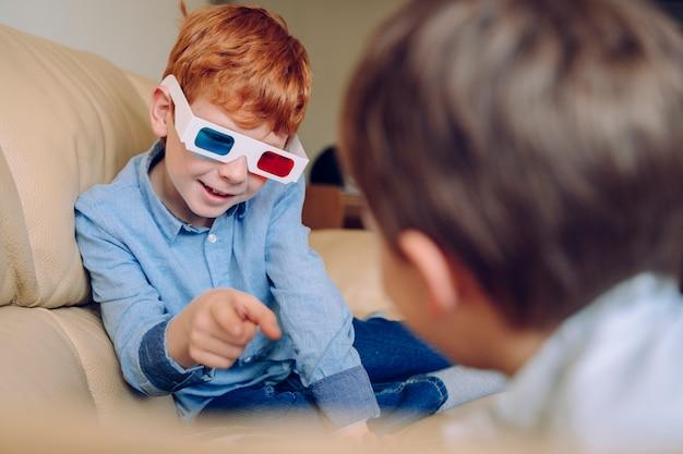 Portret van een kleine jongen die op zijn broer een educatief driedimensionaal boek wijst. vrolijke jongen spelen met driedimensionale bril en interactieve bioscoop thuis. vrije tijd en films