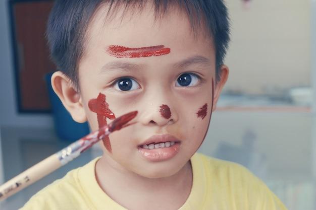 Portret van een kleine jongen die van zijn het schilderen geniet. opleiding