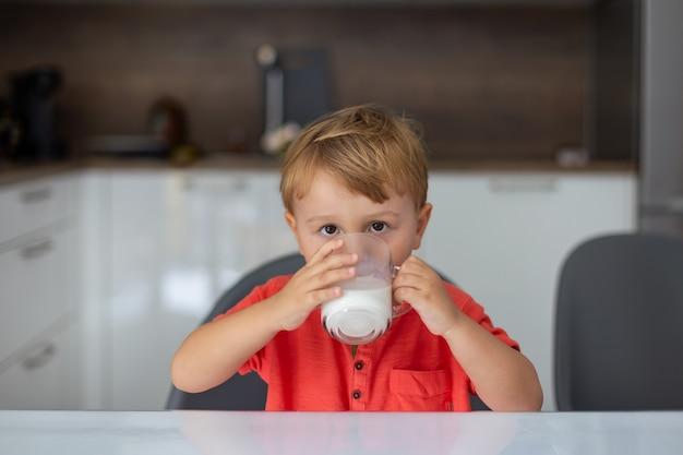 Portret van een kleine jongen drinkig melk in de ochtend. kind zit aan de tafel in de keuken en neemt gezond ontbijt.