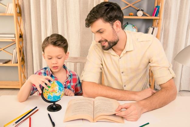 Portret van een kleine jongen en zijn vader die thuis aardrijkskunde leren