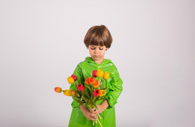 Portret van een kleine jongen in een groene regenjas met een boeket kleurrijke tulpen op een witte achtergrond met een plek voor tekst