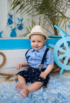 Portret van een kleine jongen in een pak en een strohoed die dichtbij een houten boot zitten