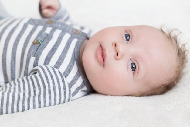 Portret van een kleine jongen in een pet op een wit