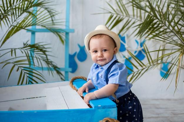 Portret van een kleine jongen in een strooien hoed en blauw shirt staat in de buurt van een houten boot op een oppervlak met een marien decor