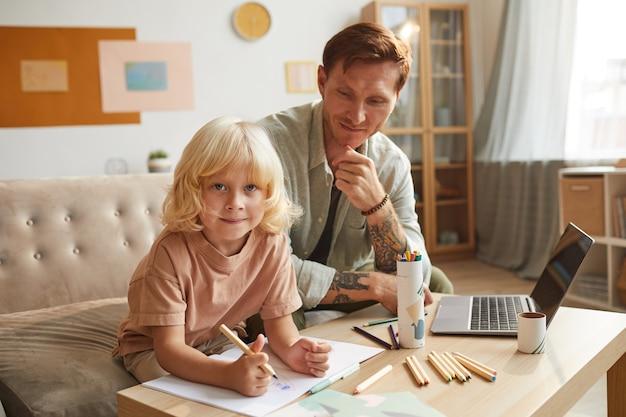 Portret van een kleine jongen met blond haar kijken tijdens het tekenen aan de tafel samen met zijn vader thuis