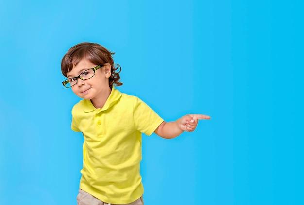 Portret van een kleine jongen met een bril op een blauwe achtergrond