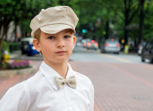 Portret van een kleine jongen met een vlinderdas en een hoed in het park met een onscherpe achtergrond