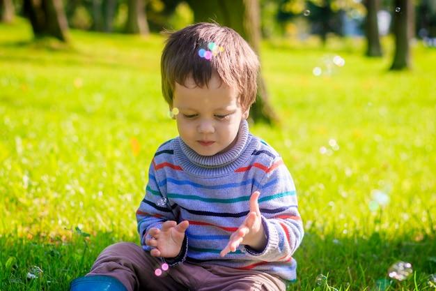 Portret van een kleine jongen op een achtergrond van gras. kleine jongen in een trui.