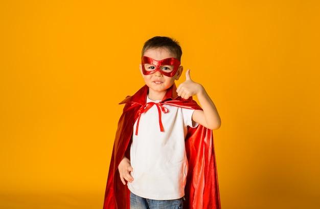 Portret van een kleine jongen-peuter in een heldenkostuum met een rood masker en een cape toont de klas met zijn hand op een geel oppervlak met ruimte voor tekst