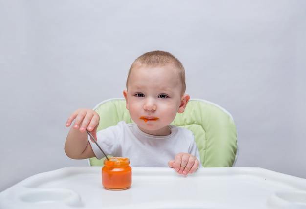 Portret van een kleine jongenszitting bij een lijst en het eten van zijn eigen wortelpuree op een geïsoleerd wit