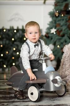 Portret van een kleine jongenszitting op een uitstekend stuk speelgoed vliegtuig dichtbij een kerstboom. kerst versiering. de jongen verheugt zich op zijn kerstcadeau. vrolijk kerstfeest en een gelukkig nieuwjaar