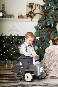 Portret van een kleine jongenszitting op een uitstekend stuk speelgoed vliegtuig dichtbij een kerstboom