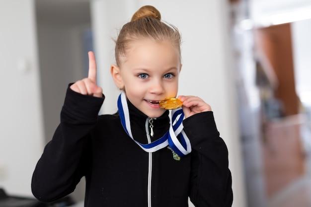 Portret van een kleine meisjesturner in een trainingspak met medailles op de nek, bijtend op de medaille en duimen opdagen