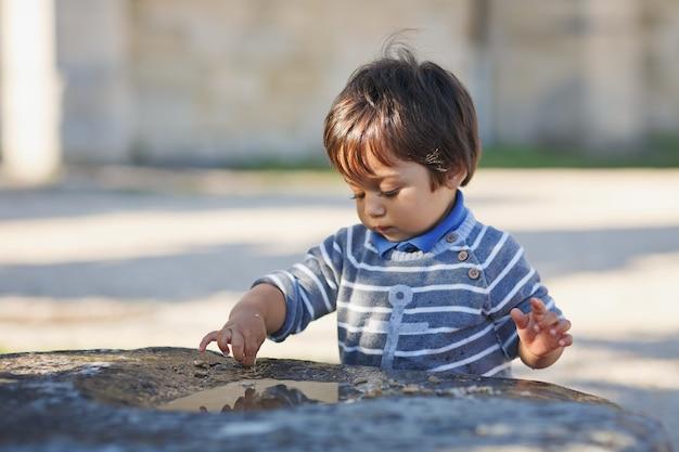 Portret van een kleine oostelijke knappe babyjongen buiten spelen in het park