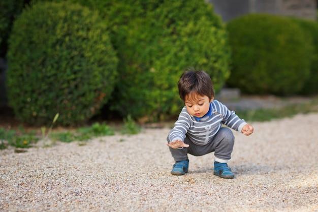 Portret van een kleine oostelijke knappe babyjongen die met kiezelstenen buiten in het park speelt. arabische kinderpret op straat met kiezelstenen.