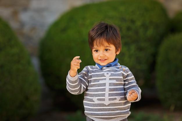 Portret van een kleine oostelijke knappe babyjongen die met kiezelstenen buiten in het park speelt. arabische kinderpret op straat.