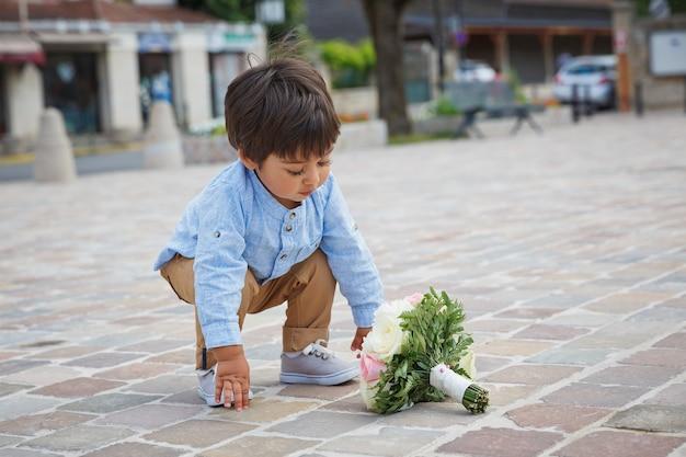 Portret van een kleine oosterse knappe babyjongen die buiten speelt met een boeket bloemen.