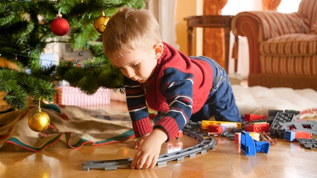Portret van een kleine peuterjongen die een spoorweg bouwt en speelt met een speelgoedtrein onder de kerstboom