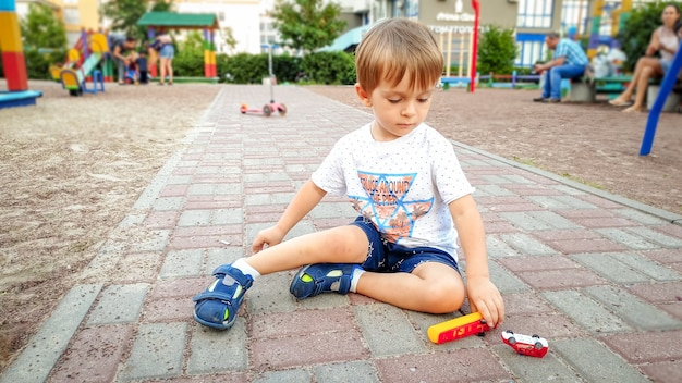 Portret van een kleine peuterjongen die met speelgoedauto's speelt op de speelplaats