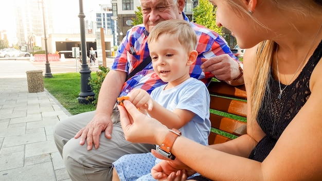 Portret van een kleine peuterjongen met een jonge moeder en gradfather die op de bank in het park zit en speelt met een kleine plastic speelgoedhelikopter