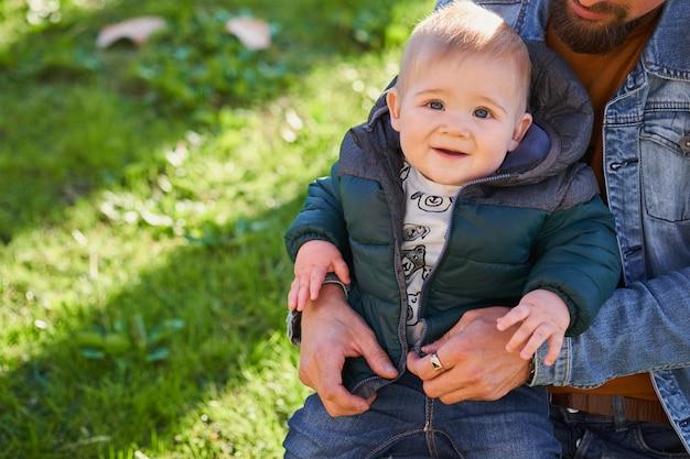 Portret van een kleine schattige jongen die op de knieën van zijn vader zit