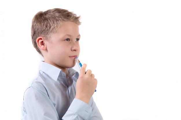 Portret van een kleine schooljongen in een peinzende pose geïsoleerd op wit