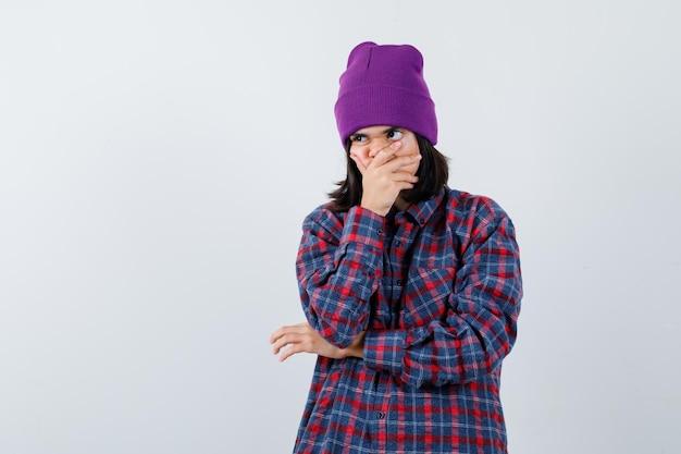 Portret van een kleine vrouw die de hand op de mond houdt in een geruit hemd en er attent uitziet