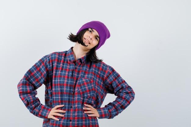 Portret van een kleine vrouw die haar handen op de heup houdt in een geruit hemd en een muts die er gelukkig uitziet