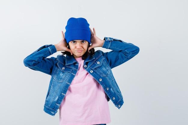 Portret van een kleine vrouw die handen op het hoofd houdt