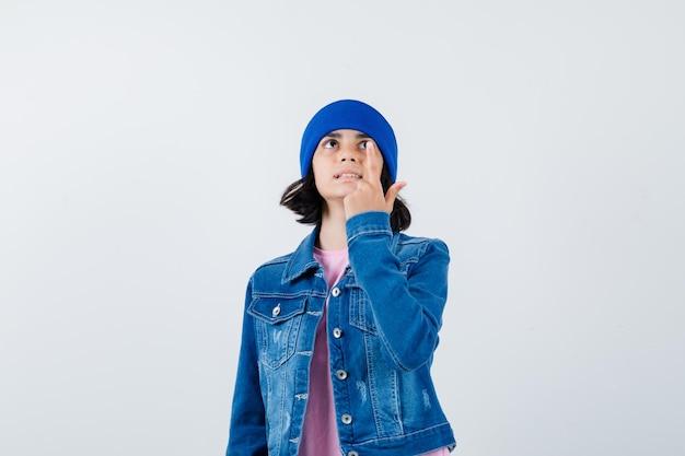 Portret van een kleine vrouw die omhoog wijst in een spijkerjasje en een muts die er positief uitziet