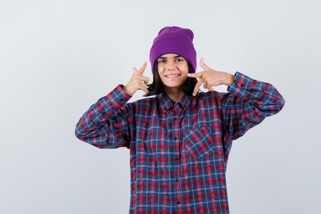 Portret van een kleine vrouw die opzij wijst in een geruit overhemd en een muts die er gelukkig uitziet
