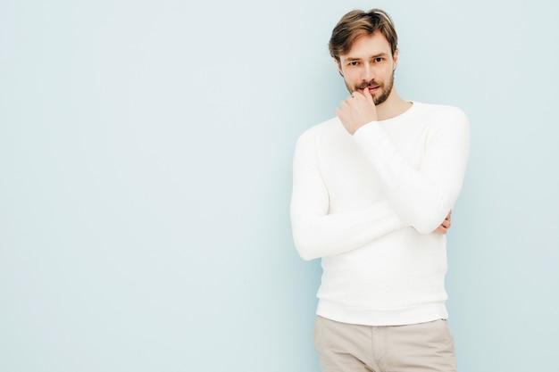 Portret van een knap glimlachend hipster-houtseksueel zakenmanmodel met een casual witte trui en broek