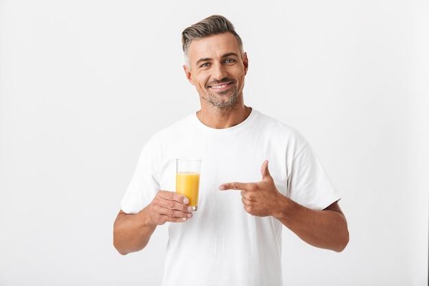 Portret van een knappe 30-jarige man met borstelharen die een casual t-shirt draagt met een glas sinaasappelsap op wit wordt geïsoleerd