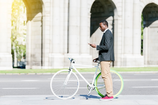 Portret van een knappe afrikaanse man die lacht wanneer hij zijn mobiel op straat gebruikt.