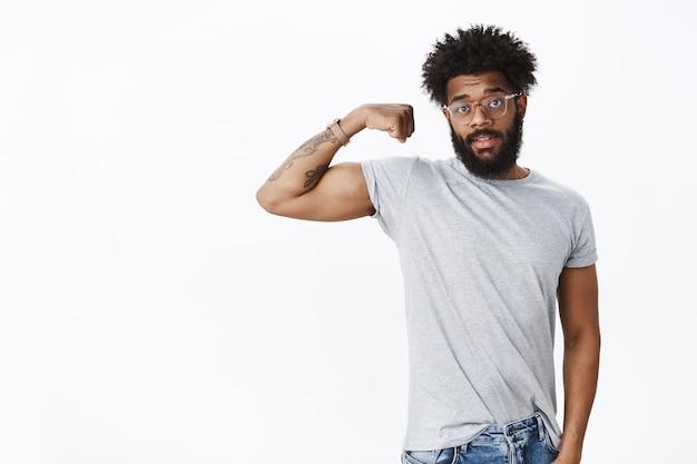 Portret van een knappe afro-amerikaanse gewone bebaarde man met krullend haar in een bril die één hand opheft en pronkende biceps die sterk zijn als trainen in de sportschool en mensen uitnodigen om mee te doen