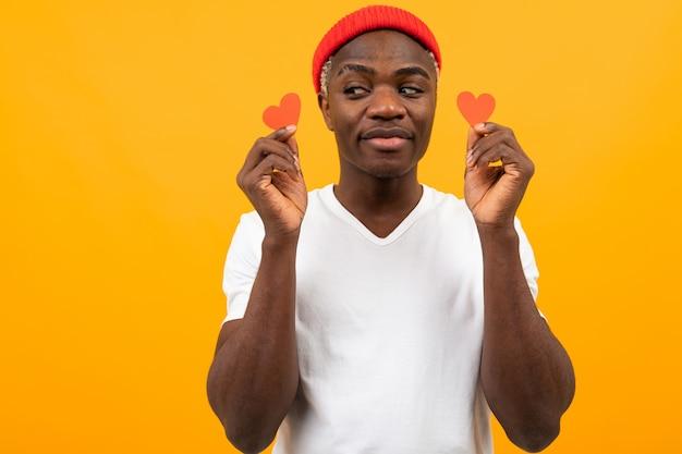 Portret van een knappe amerikaanse donkere man in een wit t-shirt met twee kleine hartvormige ansichtkaarten voor valentijnsdag op een gele achtergrond