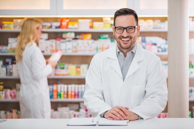 Portret van een knappe apotheker aan het loket van een drogisterij, vrouwelijke collega werken