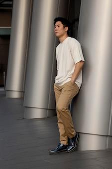 Portret van een knappe aziatische man die buiten in de stad poseert