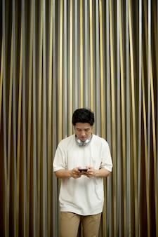 Portret van een knappe aziatische man die buitenshuis smartphone en koptelefoon gebruikt
