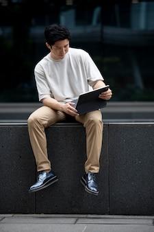 Portret van een knappe aziatische man die een laptop buiten in de stad gebruikt