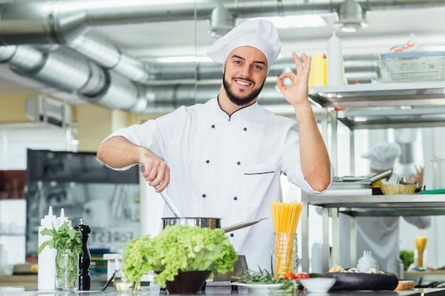 Portret van een knappe, bebaarde chef-kok die een pan vasthoudt en een goed teken maakt
