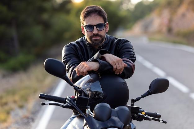 Portret van een knappe bebaarde fietser die naar de camera kijkt terwijl hij op zijn motor zit en een helm vasthoudt.