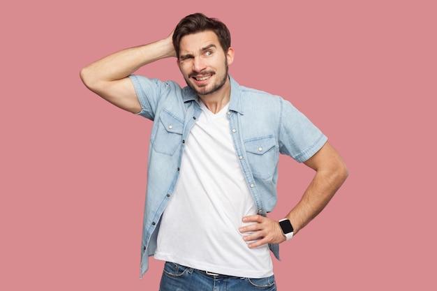Portret van een knappe, bebaarde jongeman in een blauw casual stijlshirt die staat en wegkijkt en denkt wat te doen. indoor studio opname, geïsoleerd op roze achtergrond.