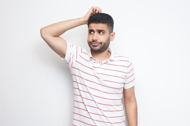 Portret van een knappe, bebaarde jongeman in een gestreept t-shirt die zijn hoofd krabt, schaaft en ergens aan denkt. indoor studio opname, geïsoleerd op een witte achtergrond.