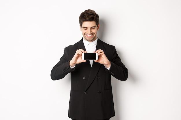 Portret van een knappe bebaarde man in een zwart pak, die je smartphonescherm laat zien en tevreden glimlacht, staande tegen een witte achtergrond