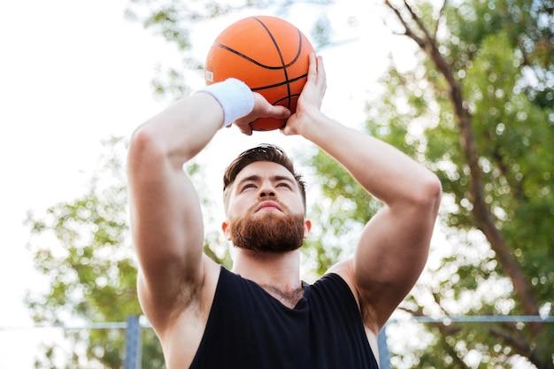 Portret van een knappe bebaarde man in sportkleding die buiten basketbal speelt