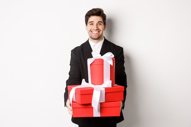 Portret van een knappe bebaarde man in trendy pak, met cadeaus voor het nieuwe jaar en glimlachend, voorbereide cadeautjes, staande op een witte achtergrond.